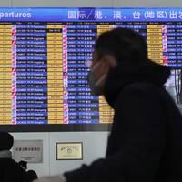 En passagerar med skyddsmask på flygplatsen i Peking tittar på avgångstavlan i terminalen. Sedan virusets utbrott har Kina begränsat möjligheterna att resa i landet