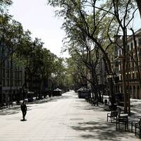 En ensam person syns promenera ned för en folktom gata i Barcelona.