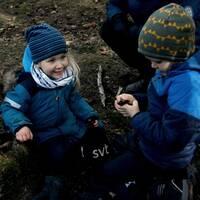 Två barn som leker i skogen.