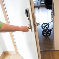 En undersköterska gläntar på en dörr till ett boende på ett äldreboende.
