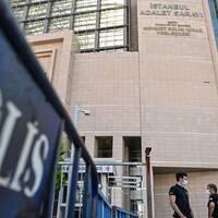 Två poliser med munskydd står utanför domstolen i Istanbul.