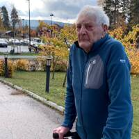 äldre man med rullator, utomhus, iklädd en fleecejacka