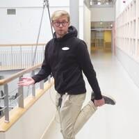 En man står i korridor och håller i sin fotled.