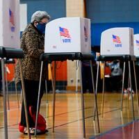 Bilden visar en äldre kvinna med munskydd som röstar i en vallokal på Morgan State University i Baltimore, Maryland. På andra bilden syns en logotyp för Google som sagt att de stoppar politiska annonser i samband med det amerikanska presidentvalet.