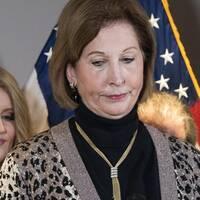 Sidney Powell ser sammanbiten ut under en presskonferens. Amerikanska flaggor syns i bakgrunden.