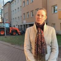 Kristina Grape utomhus i ett bostadsområde med lägenheter och bilar i bakgrunden.