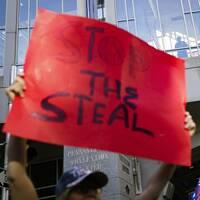 """Demonstrant som håller uppe en skylt med texten """"stoppa stölden"""""""