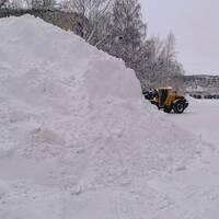 jättelik snöhög i förgrund, en fotgängare och en traktor som arbetar med snöröjning