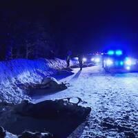 Polisbilar med blåljus och folk på en snöig väg med branta plogvallar, mörkt ute. Flera döda renar ligger längs vägkanten.