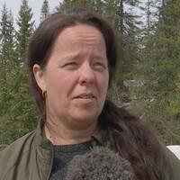 en kvinna som intervjuas i framför skogsparti, snö på marken