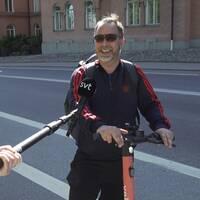 På bilden syns två män på elsparkcyklar. I förgrunden syns två händer som håller en lång pinne med en mikrofon som det står SVT på.