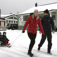En man och en kvinna går på en snöig väg. Kvinnan drar två små barn på en bob. I bakgrunden syns villor.
