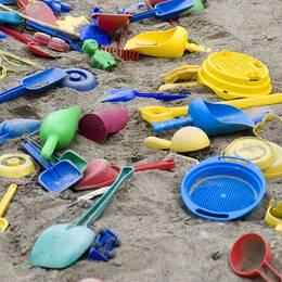 Plastleksaker i en sandlåda.
