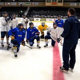 Damlaget lyssnar till tränaren i hockeyrinken.