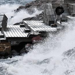 En man tittar på vågorna vid Scaniabadet i Malmö.