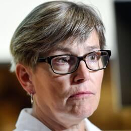 Kortklippt kvinna med glasögon till vänster, provrör med lock i lila, turkos och blått.