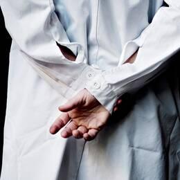 Läkare i vit rock står med armarna bakom ryggen.