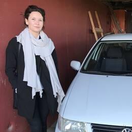 Kvinna och bil i ett garage.