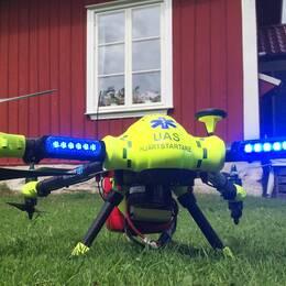 En drönare i klargula färger har landat framför en man som gör hjärt-lungräddning på en medvetslös person.