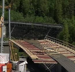 vy över järnvägsbro som byggs, och en järnvägsbank, i skogen