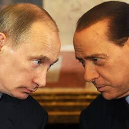 Rysslands president Vladimir Putin lutar sig mot Italiens förre premiärminister Silvio Berlusconi