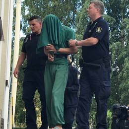 fängslad man med duk över huvudet förs in i byggnad av två vakter