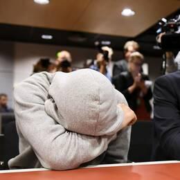 En av de misstänkta för inblandning i knivattacken i Åbo under häktningsförhandlingen. Han döljer sitt ansikte.