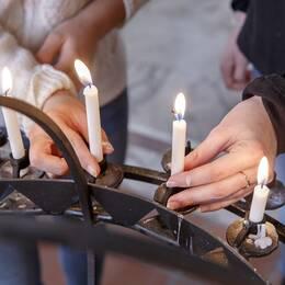 Två tjejer tänder ljus i kyrkan.