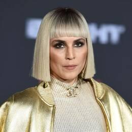 Skådespelaren Noomi Rapace i guldjacka, guldtröja och guldhalsband.