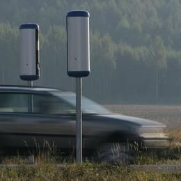 En bil kör förbi vägkameror.