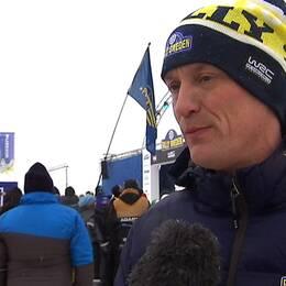 Glenn Olsson tittar snett förbi kameran. I bakgrunden syns människor