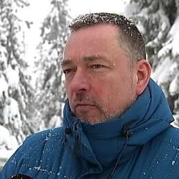 en man i dunjacka framför snöig skog