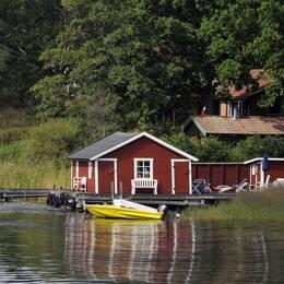 Bild på sommarstuga vid vattnet samt landsbygdsministern Sven-Erik Bucht (S).