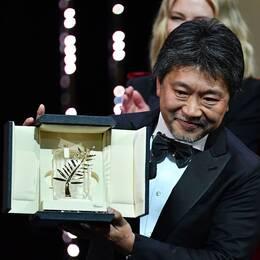Regissör Hirokazu Kore-Eda tar emot Guldpalmen för filmen Shoplifters i Cannes.