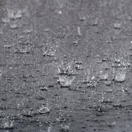 tunga vattendroppar faller på vattenfyld gata