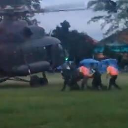 En bår bärs mot en helikopter efter räddningen ur grottan.