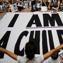 """Barn sitter med plakat och en banderoll där det står """"Jag är ett barn"""""""