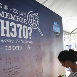 En ung tjej skriver ett kondoleansbudskap på en affisch som påminner om årsdagen av dagen då planet MH370 försvann.