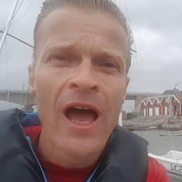 Reporter i bild , med hus och vatten bakom