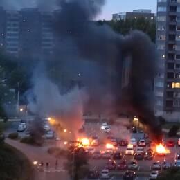 Bilar som brinner på parkeringen och ett stort rökmoln som stiger upp mot himlen.