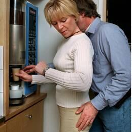 Tafsande man vid kaffautomat.