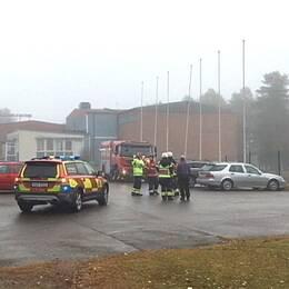utryckningsfordon och personal utanför en tegelbyggnad, dimmigt väder