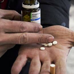 En person håller ett gäng tabletter i sin hand.