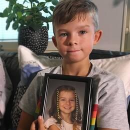 Max håller i en bild på hur han såg ut när han var Minea.