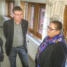 tre män och en kvinna står i grupp i en korridor