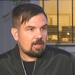Philip Naskret, reporter på SVT, utanför hus med SVT-logga