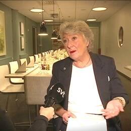Reportern syns till vänster i bild, och håller fram mikrofonen mot stadsdelsdirektören, som är klädd i svart kavaj. I bakgrunden syns ett uppdukat restaurangbord.