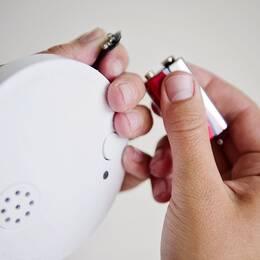 Två händer i färd med att byta batterier i en brandvarnare. Genrebild.