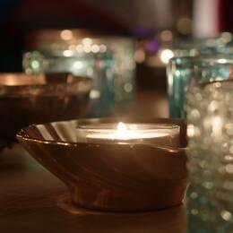 Bild på värmeljus i ljushållare.