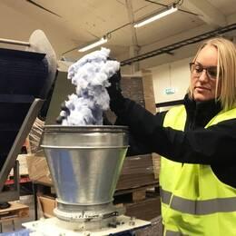 Projektledaren Alicia Björklund kör ner de söndermalda handdukarna i formeringsmaskinen.